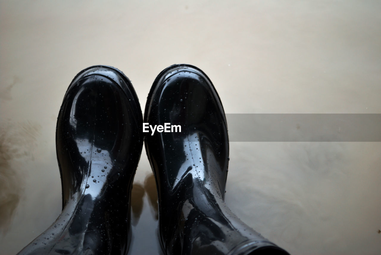 Low section of person wearing boot over water