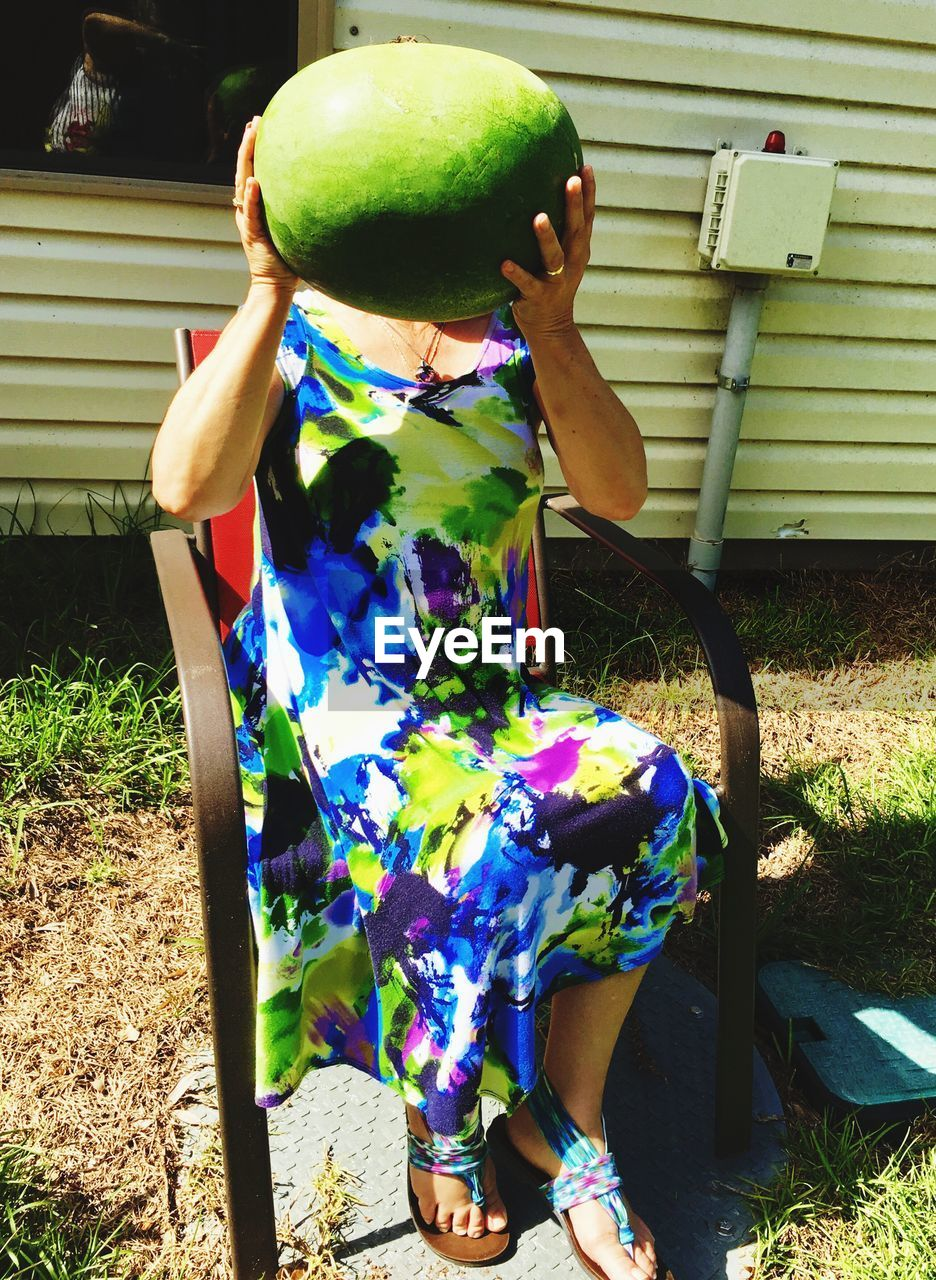 Low section of woman covering face with watermelon while sitting on chair at backyard during sunny day