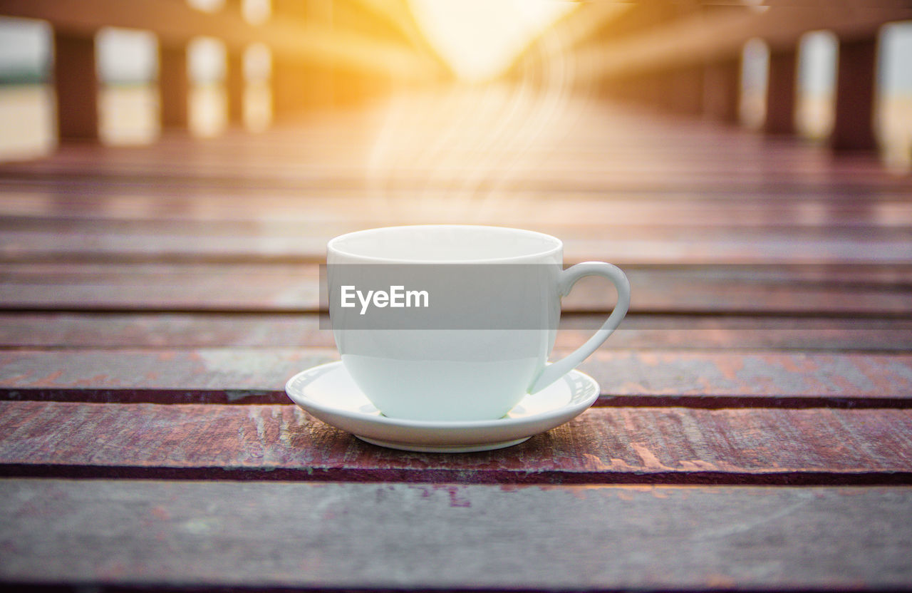 cup, mug, table, drink, refreshment, food and drink, coffee cup, wood - material, still life, coffee, close-up, saucer, no people, coffee - drink, crockery, focus on foreground, day, indoors, sunlight, selective focus, tea cup, non-alcoholic beverage