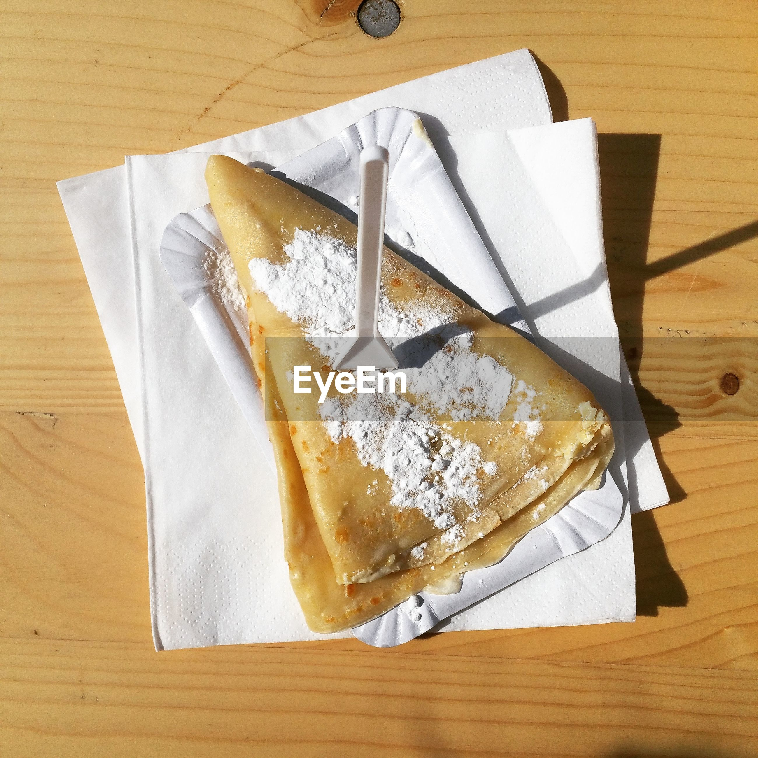 High angle view of food on tissue paper over table during sunny day