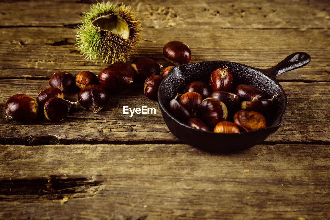 food and drink, food, freshness, table, healthy eating, wood - material, still life, fruit, wellbeing, indoors, chestnut - food, no people, chestnut, bowl, nut - food, close-up, nut, brown, high angle view, vegetable