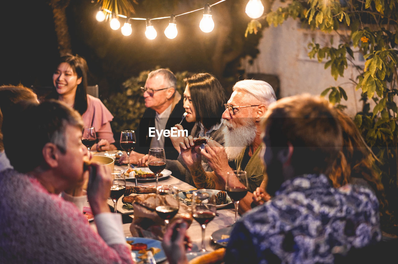 food and drink, togetherness, women, adult, men, group of people, real people, lifestyles, lighting equipment, illuminated, drink, senior adult, bonding, alcohol, males, table, food, emotion, leisure activity, females, glass, mature men, meal, dinner