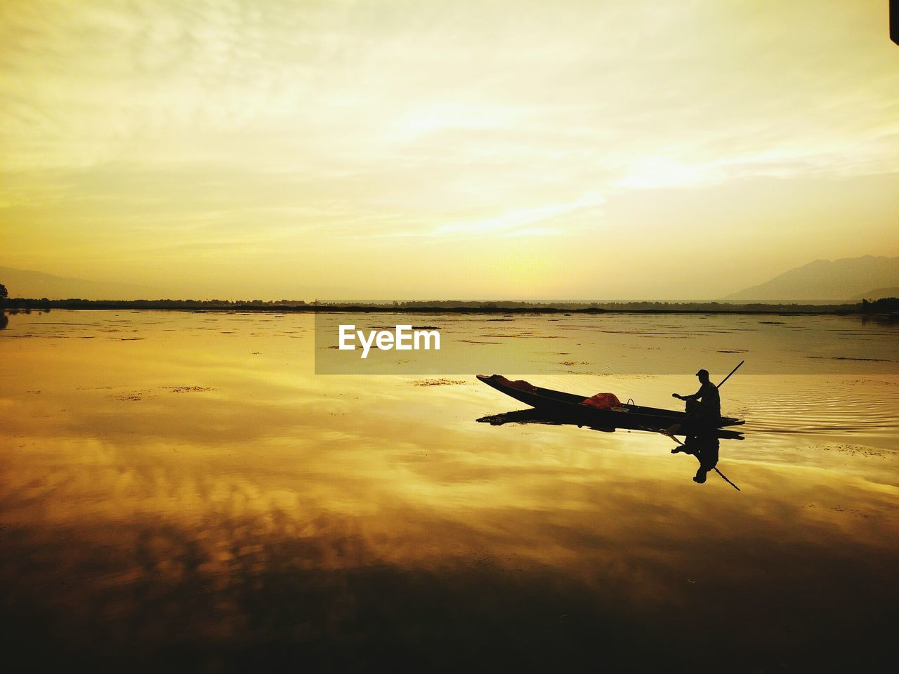 Silhouette person in boat on sea against sky during sunset