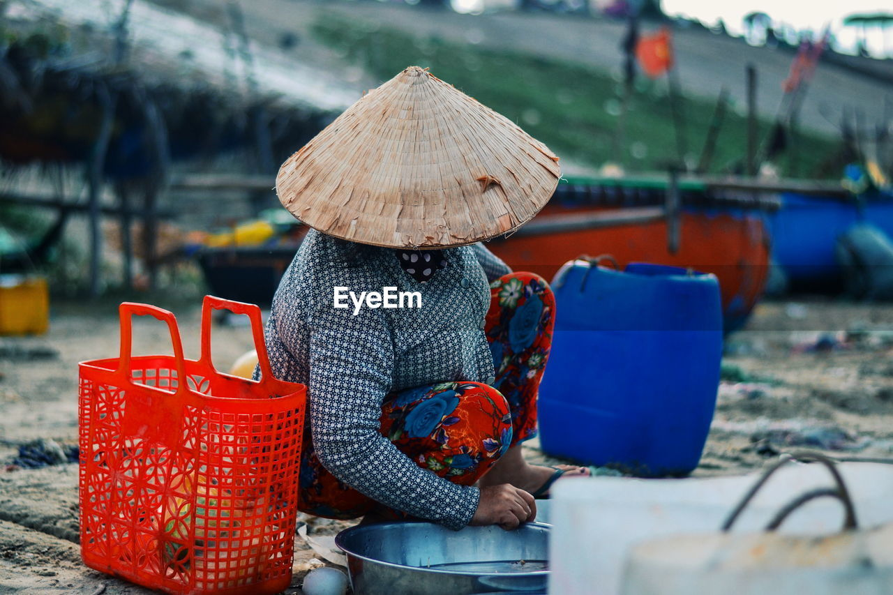 Woman Crouching By Red Basket At Fish Market