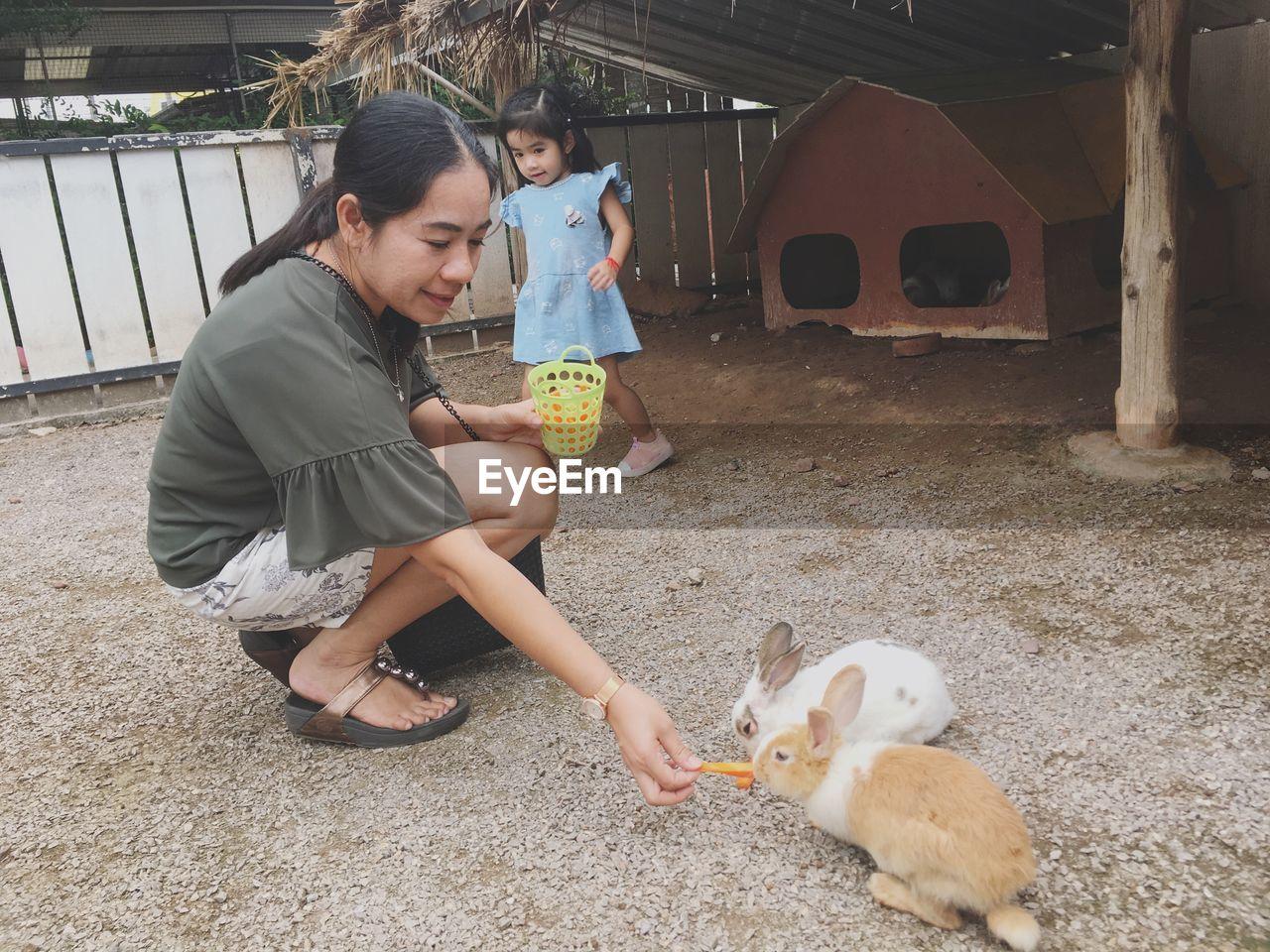 Smiling woman feeding rabbit outdoors