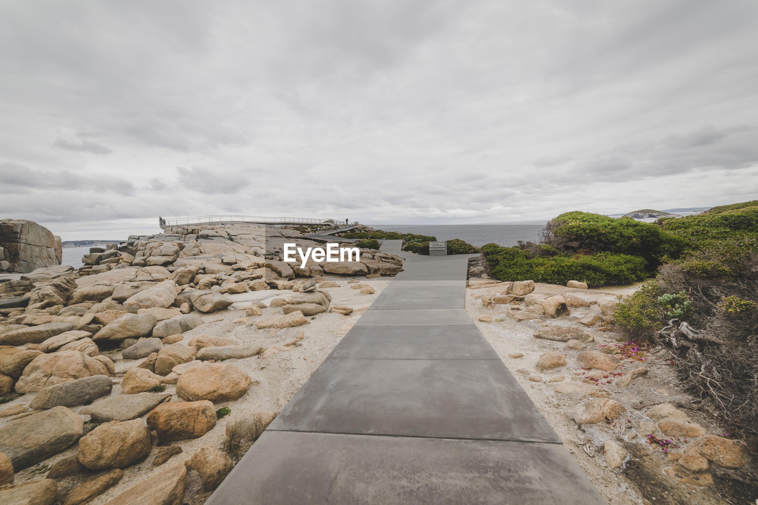 Footpath amidst rocks against sky