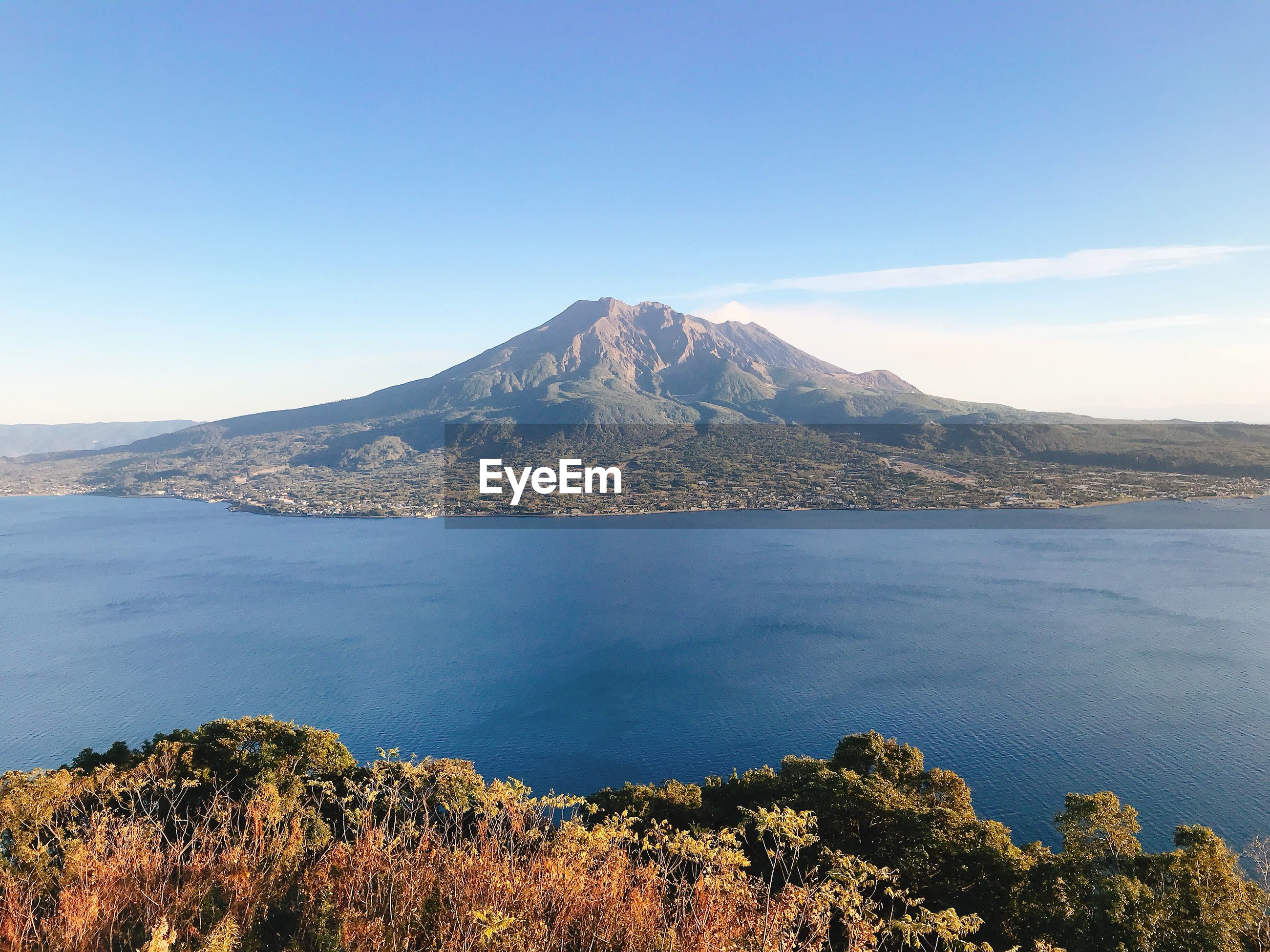 SCENIC VIEW OF SEA AND MOUNTAIN AGAINST BLUE SKY