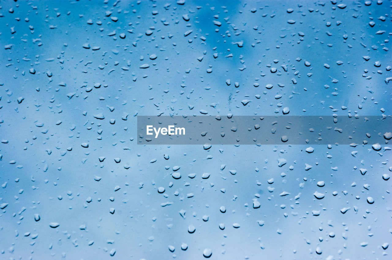 no people, blue, full frame, sky, low angle view, backgrounds, nature, day, water, wet, drop, transparent, abundance, outdoors, window, rain, beauty in nature, cloud - sky, raindrop, blue background, purity