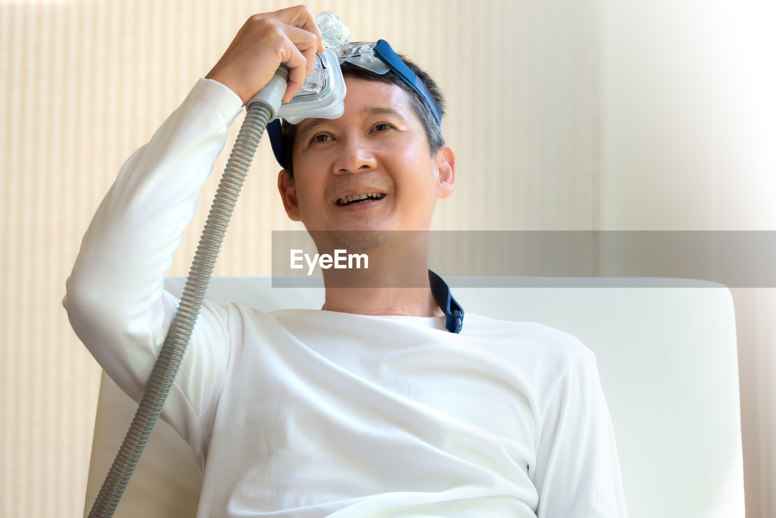 Male patient with medical oxygen equipment relaxing at hospital