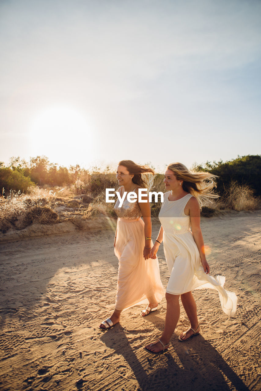 Full Length Of Friends Walking At Beach Against Sky