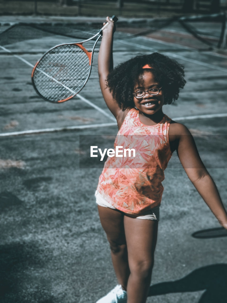 Smiling Girl Holding Racket While Standing On Court During Sunny Day