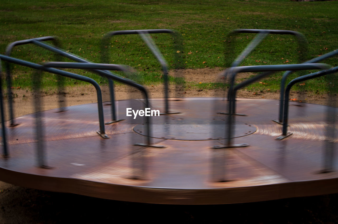no people, metal, playground, nature, day, absence, outdoors, park, blurred motion, merry-go-round, park - man made space, empty, grass, outdoor play equipment, plant, motion, wet, water