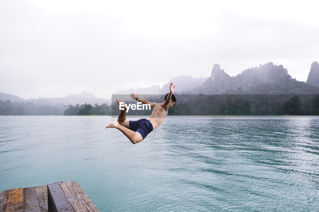 water, mid-air, one person, jumping, beauty in nature, sky, full length, leisure activity, mountain, nature, real people, day, lifestyles, diving, lake, scenics - nature, motion, vitality, outdoors, human arm
