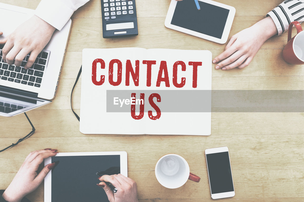 Cropped Image Of Business People With Technologies Amidst Contact Us Text On Desk