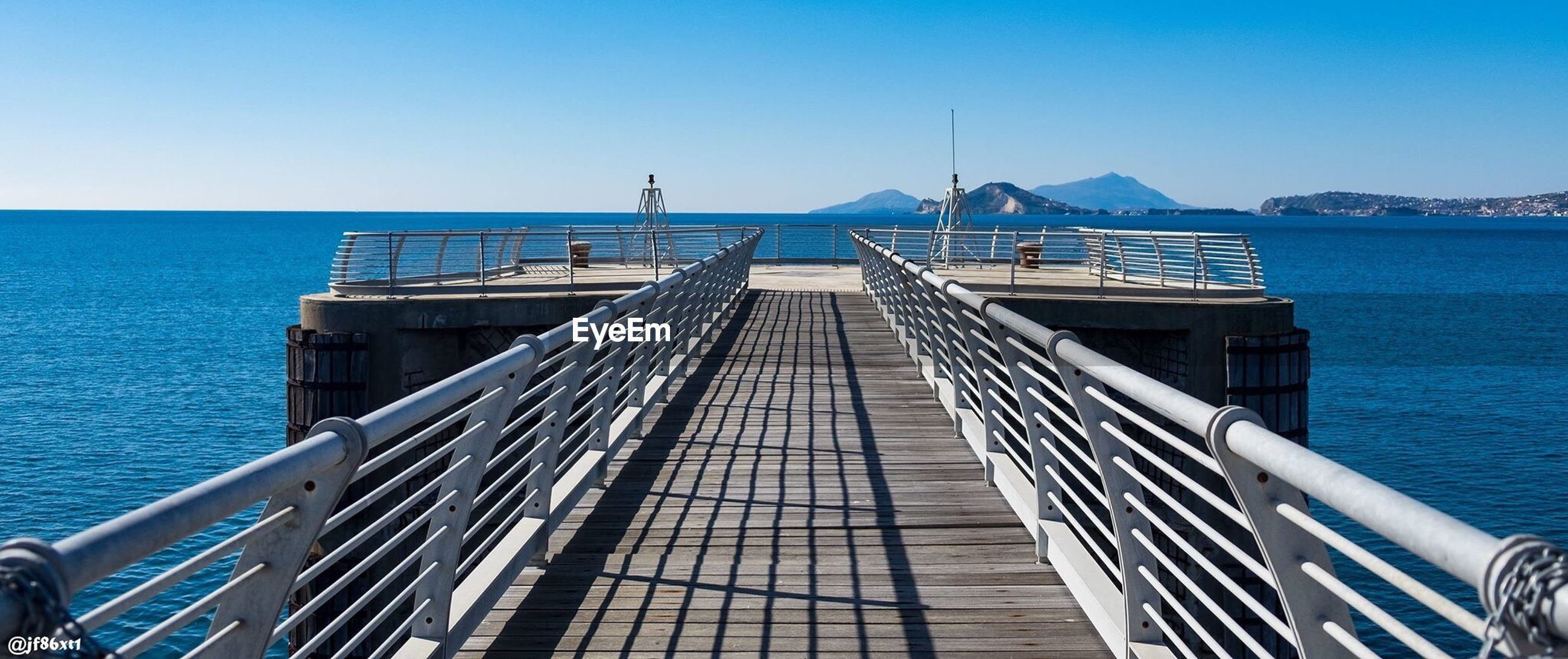 clear sky, sea, railing, blue, architecture, built structure, water, outdoors, day, beauty in nature, sky, nature, no people, horizon over water