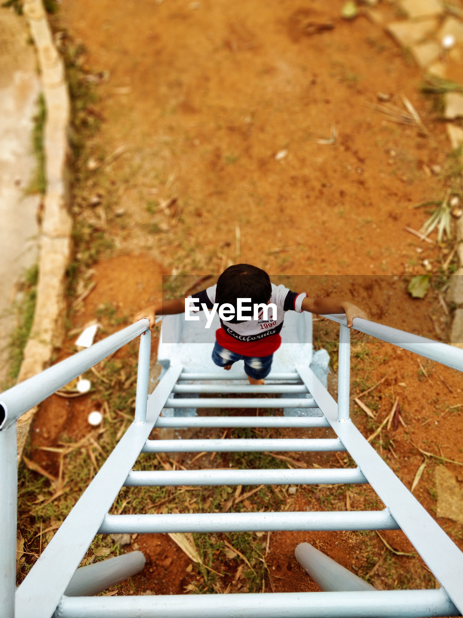 High angle view of boy on ladder