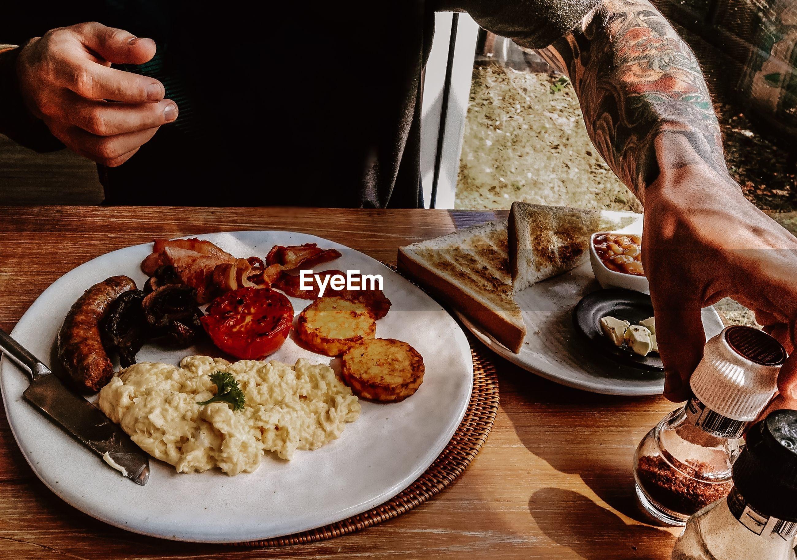 Close-up of tattooed man enjoying traditional english breakfast