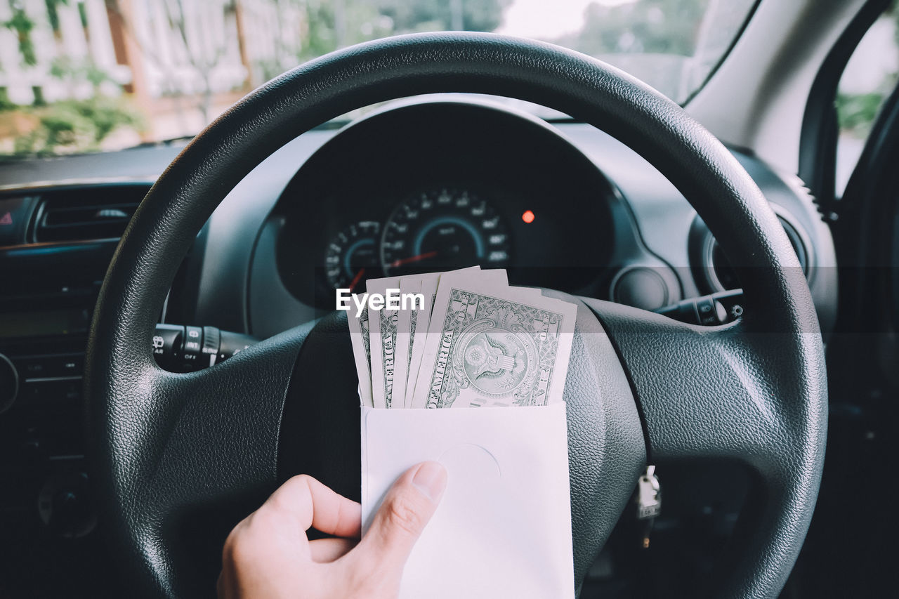 Close-Up Of Cropped Hand With Paper Currency In Car