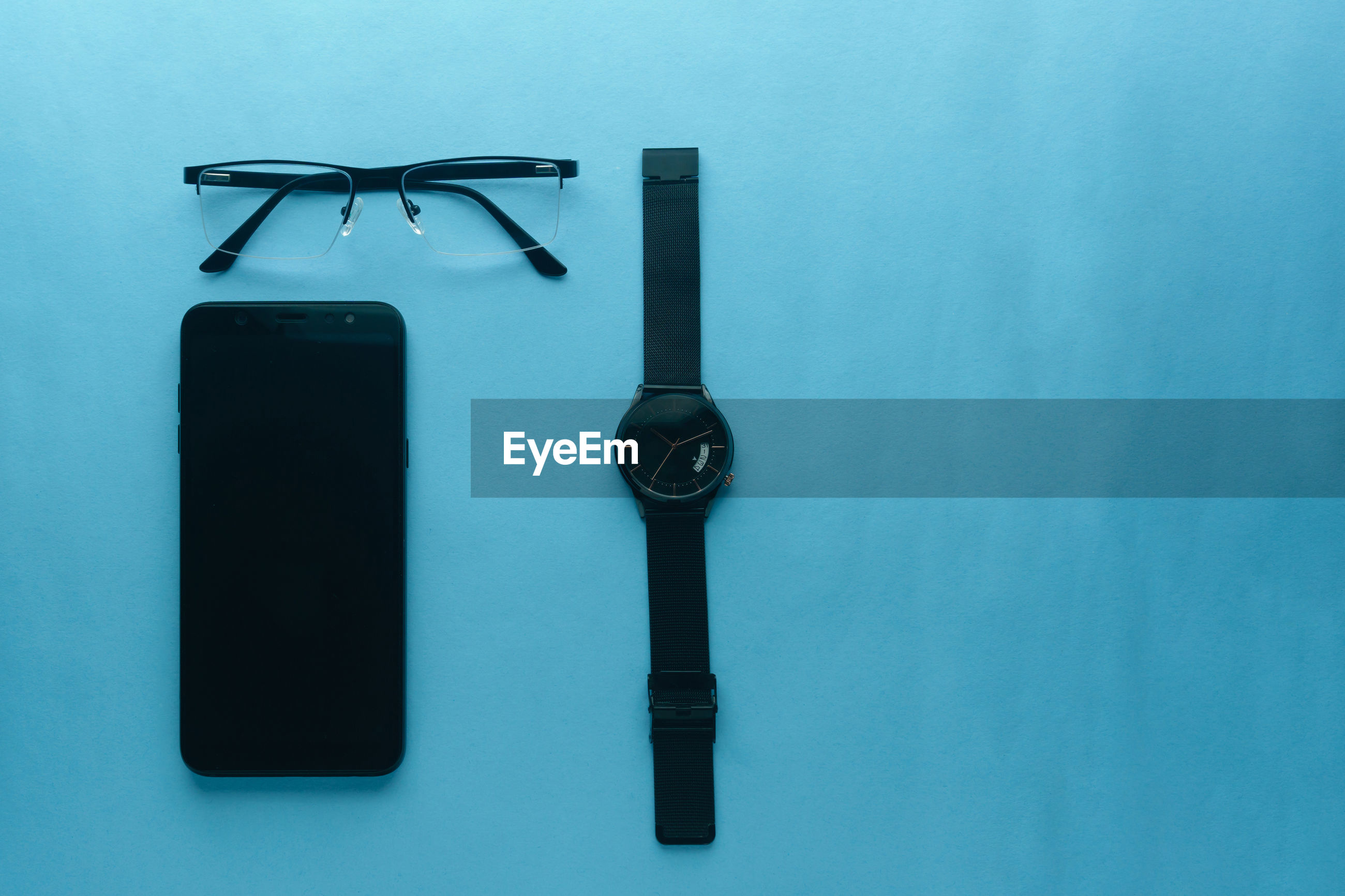 Directly above shot of gadget, eye-glasses and watch on blue table