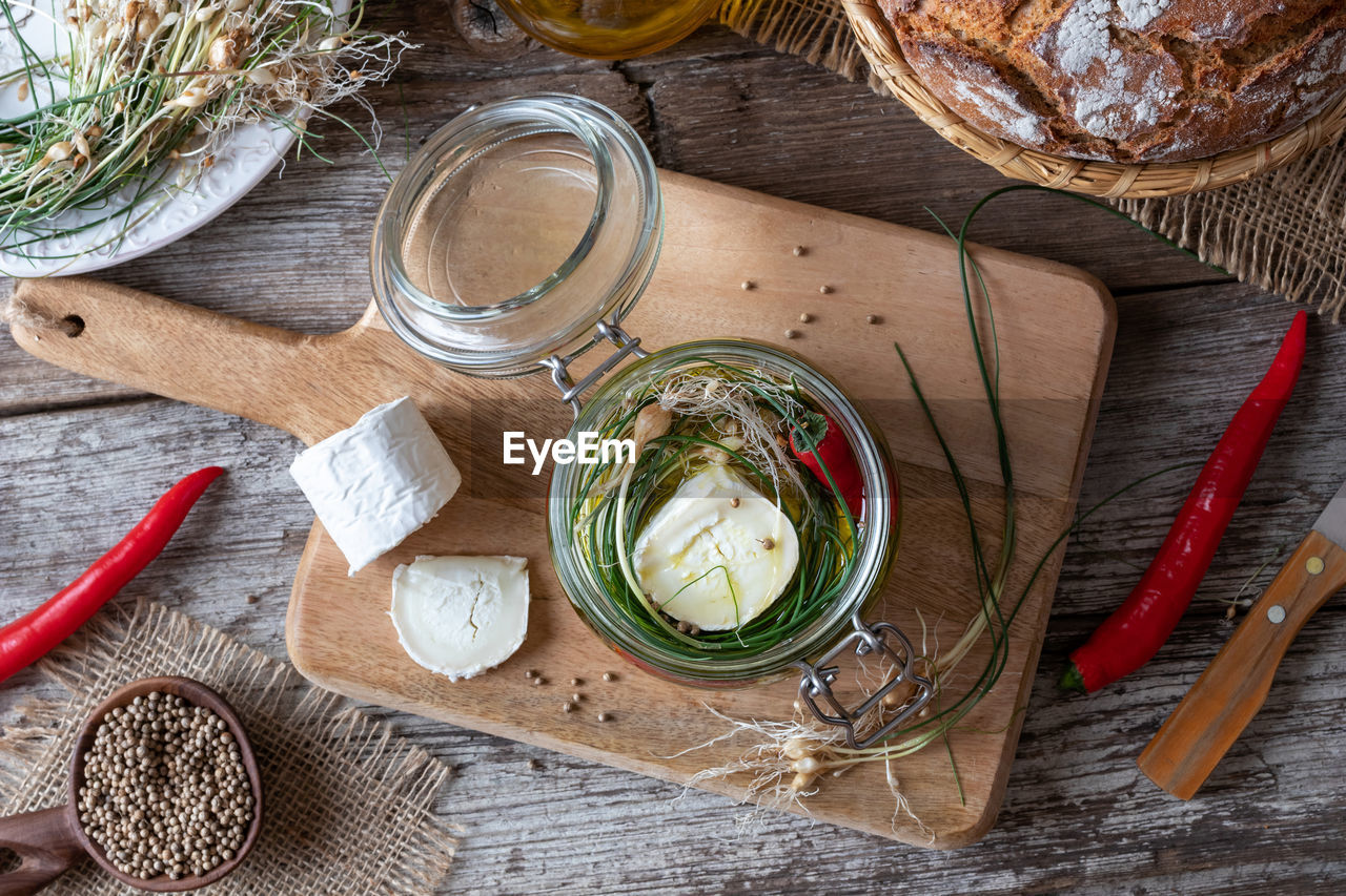 food and drink, wood - material, food, freshness, healthy eating, wellbeing, spice, dairy product, indoors, high angle view, vegetable, no people, container, herb, household equipment, kitchen utensil, table, ingredient, jar, eating utensil, preparation, glass, mediterranean food