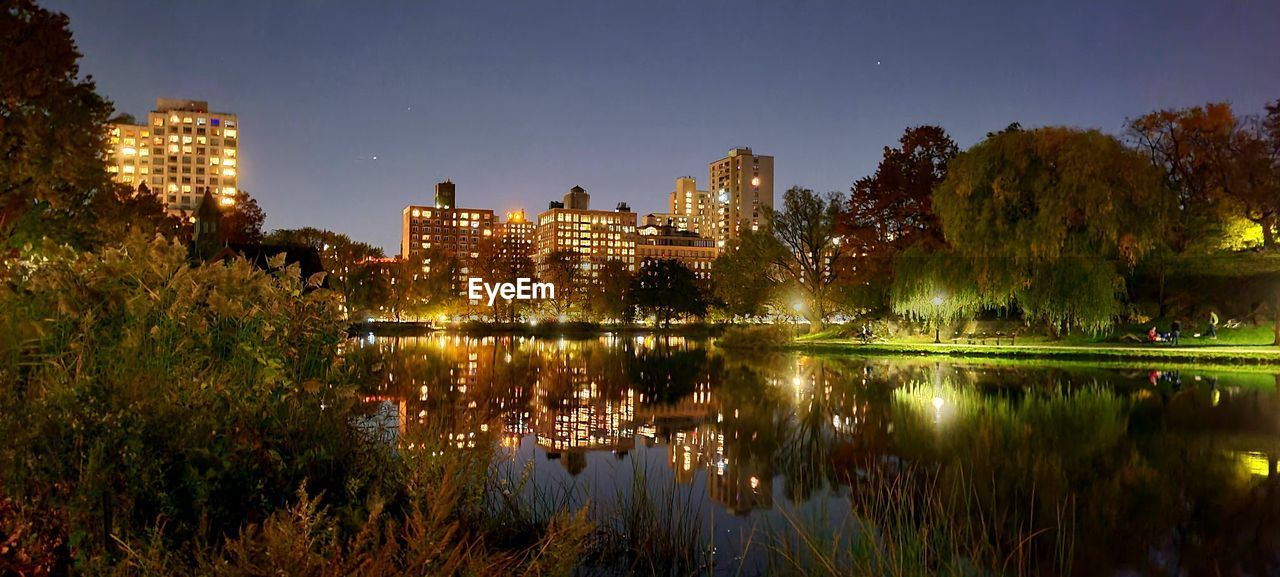 SCENIC VIEW OF LAKE BY ILLUMINATED BUILDINGS AGAINST SKY