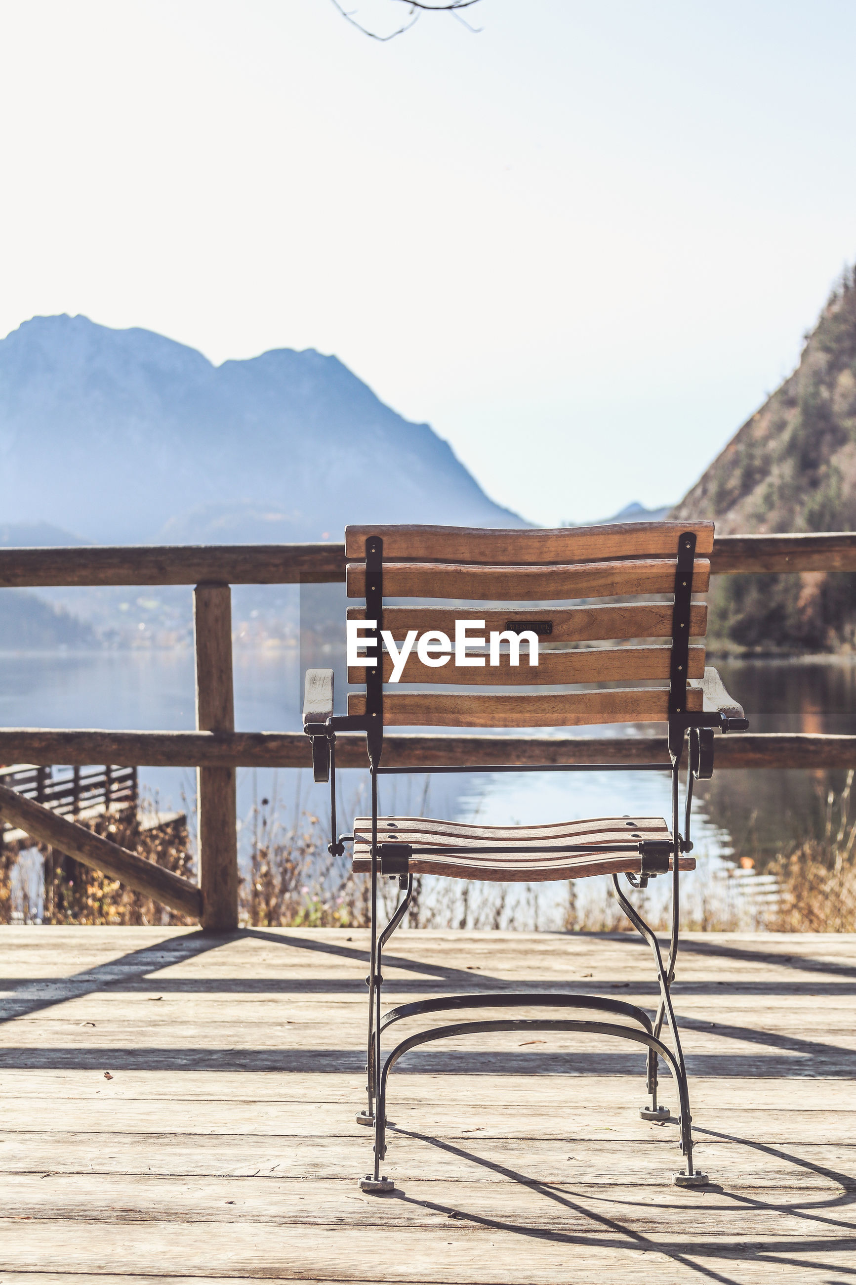 EMPTY CHAIRS AND TABLE AGAINST MOUNTAINS