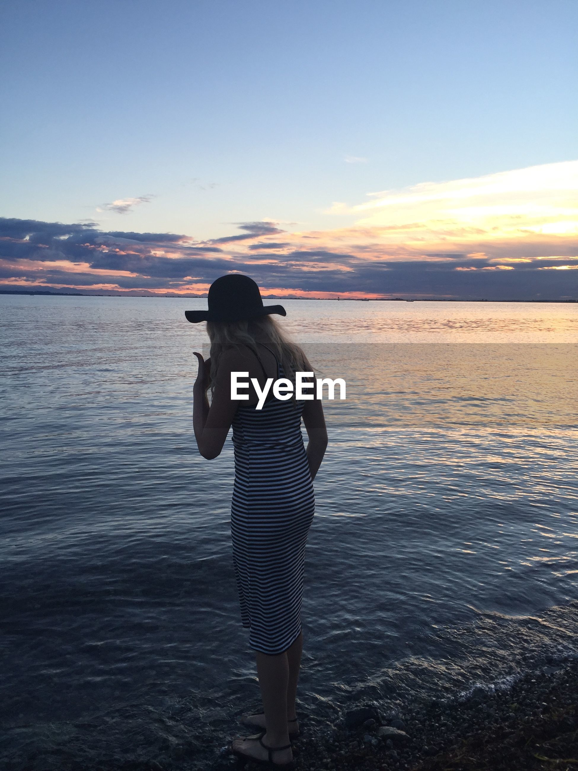 Rear view of teenage girl standing by sea against sky during sunset