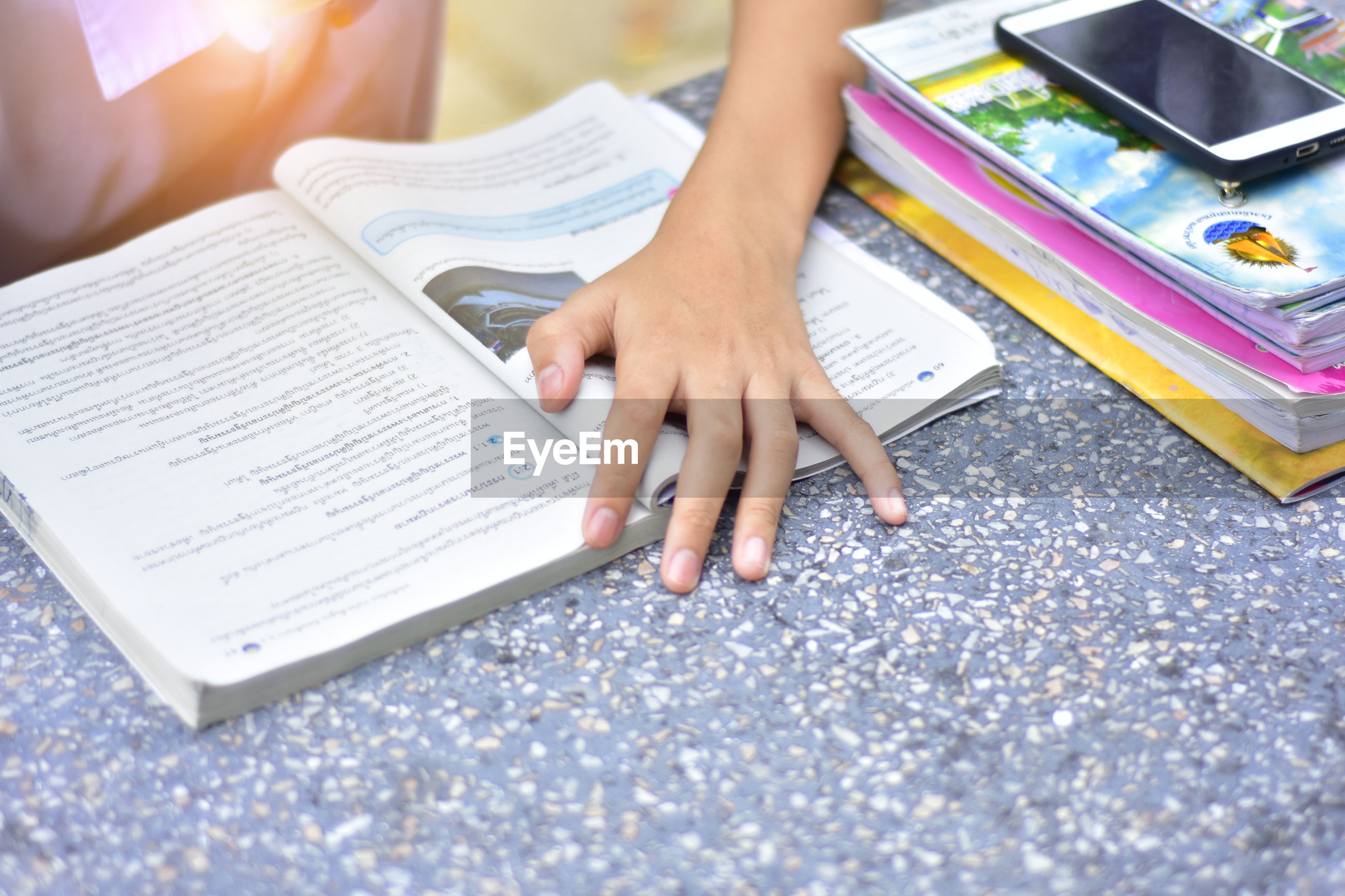 Midsection of student reading book at table