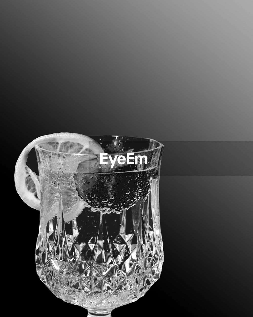 Close-up of drinking glass against gray background