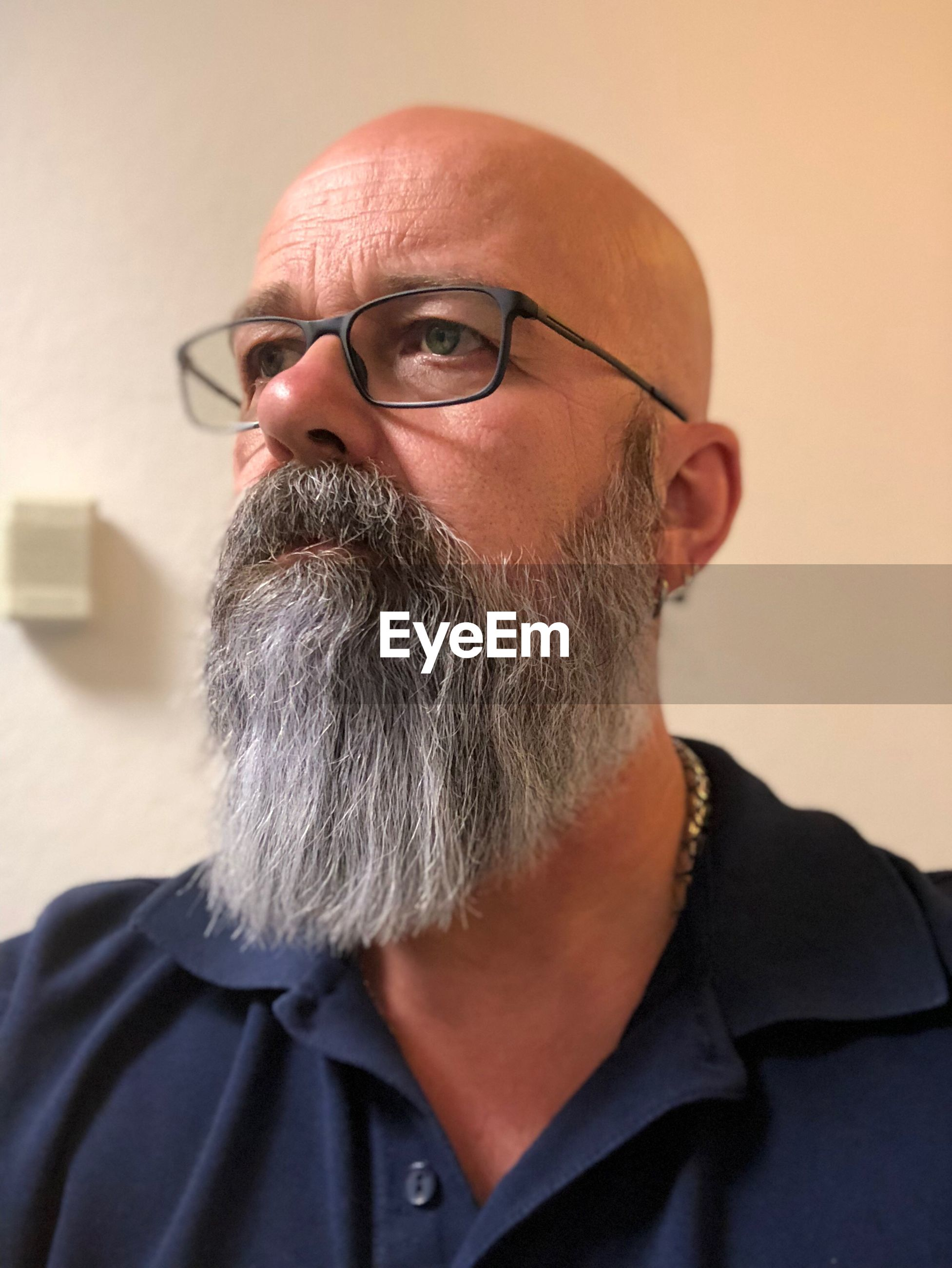 Bearded mature man wearing eyeglasses against wall at home