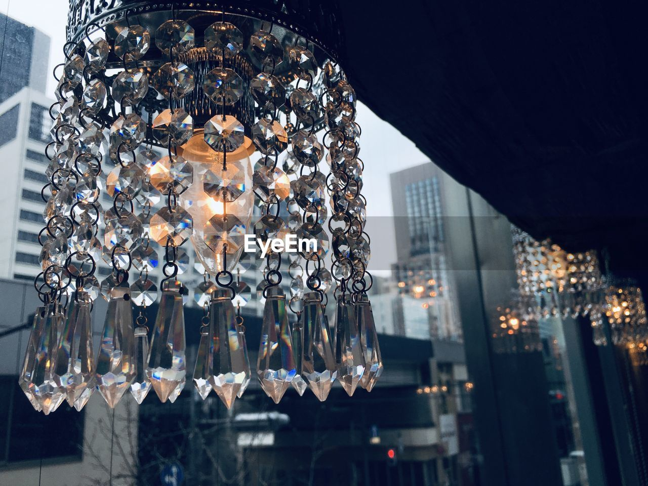 LOW ANGLE VIEW OF ILLUMINATED CHANDELIER HANGING IN CITY