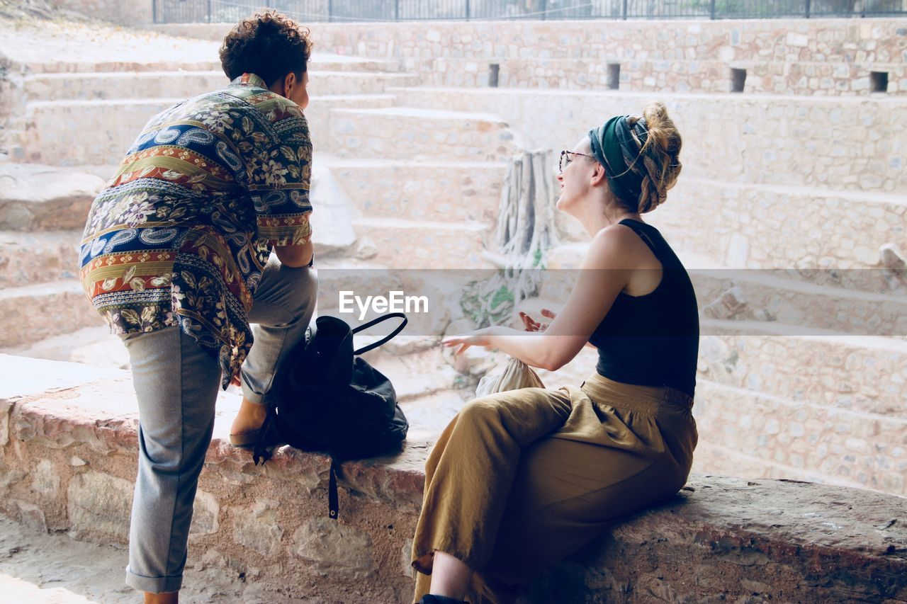 two people, day, sitting, real people, togetherness, outdoors, full length, architecture, friendship, animal themes, adult, people