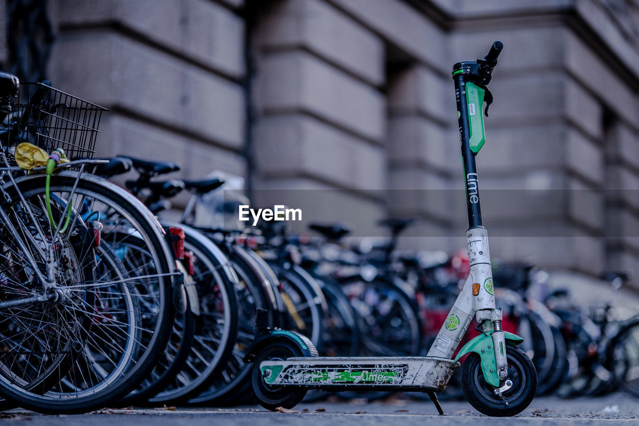 transportation, mode of transportation, land vehicle, bicycle, stationary, no people, focus on foreground, city, architecture, green color, day, street, parking, built structure, building exterior, outdoors, wheel, close-up, selective focus, basket