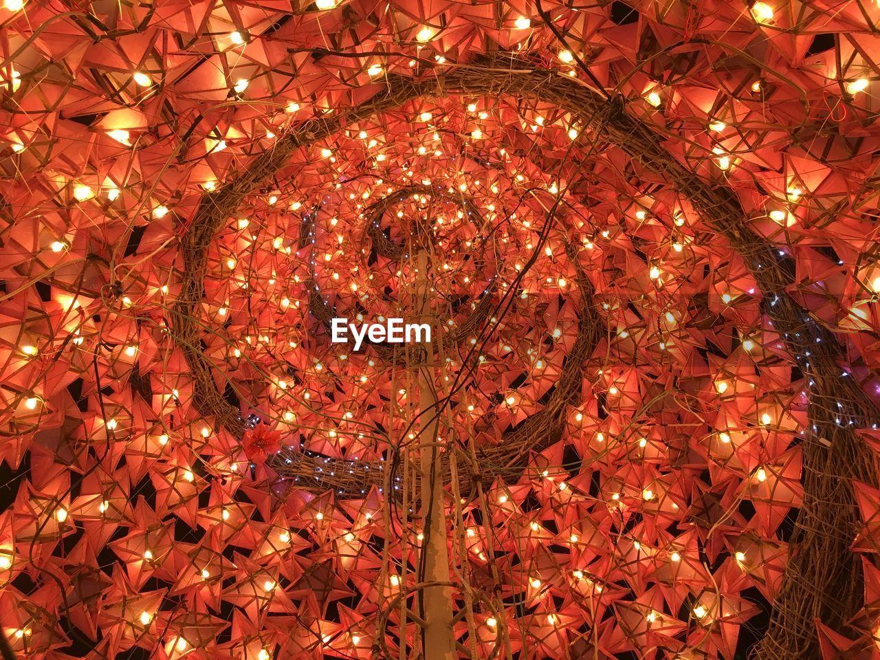 LOW ANGLE VIEW OF ILLUMINATED LANTERNS HANGING ON CHRISTMAS LIGHTS