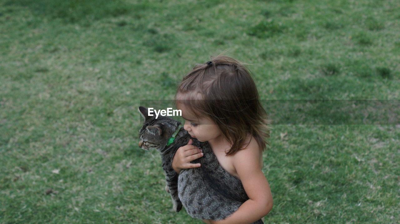 Girl Holding Cat Standing On Grass