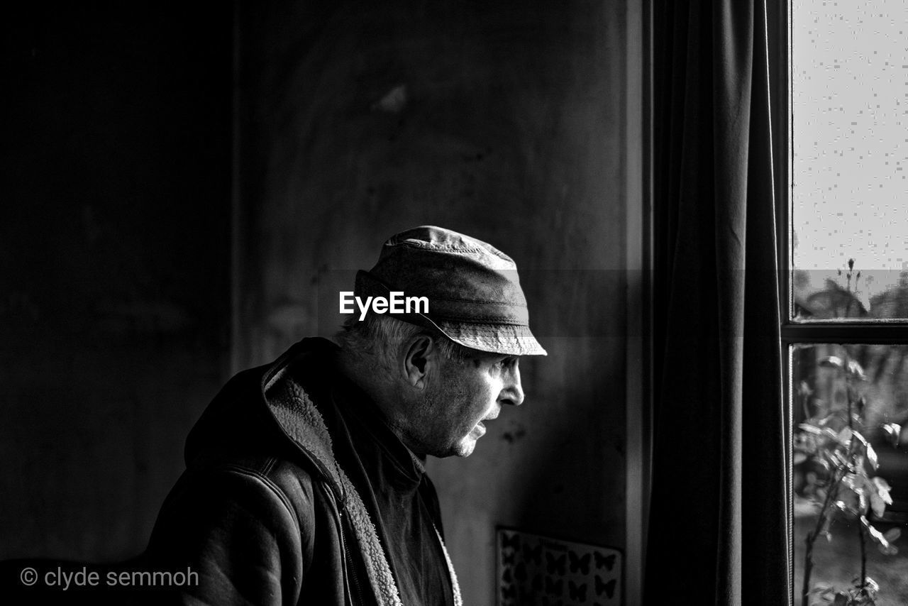 one person, real people, window, side view, looking, men, hat, lifestyles, portrait, looking away, headshot, adult, clothing, day, leisure activity, focus on foreground, mature adult, indoors, mature men, contemplation, profile view