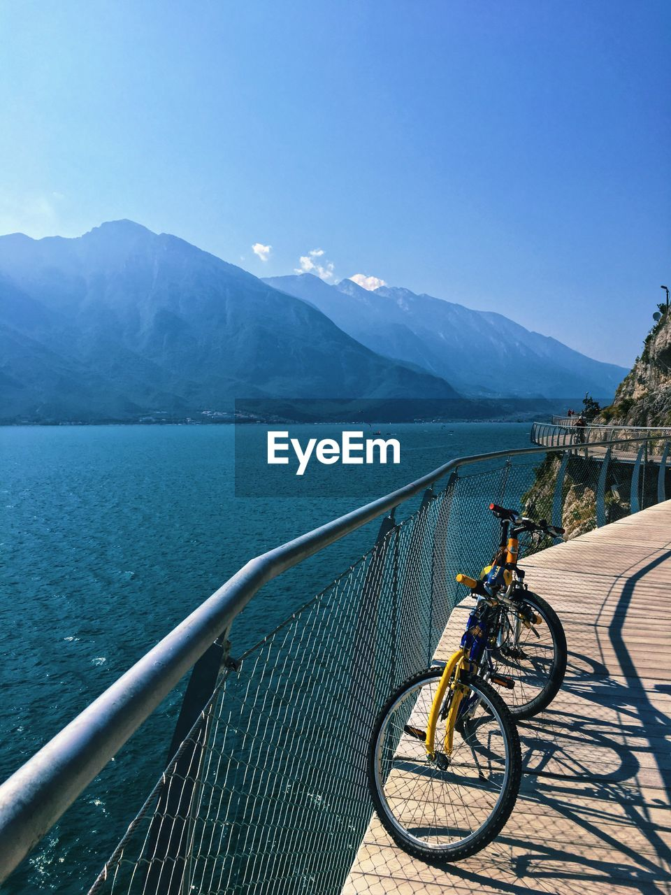 transportation, bicycle, mountain, water, mode of transportation, sky, land vehicle, nature, railing, beauty in nature, activity, day, mountain range, architecture, sport, sunlight, scenics - nature, travel, blue, outdoors