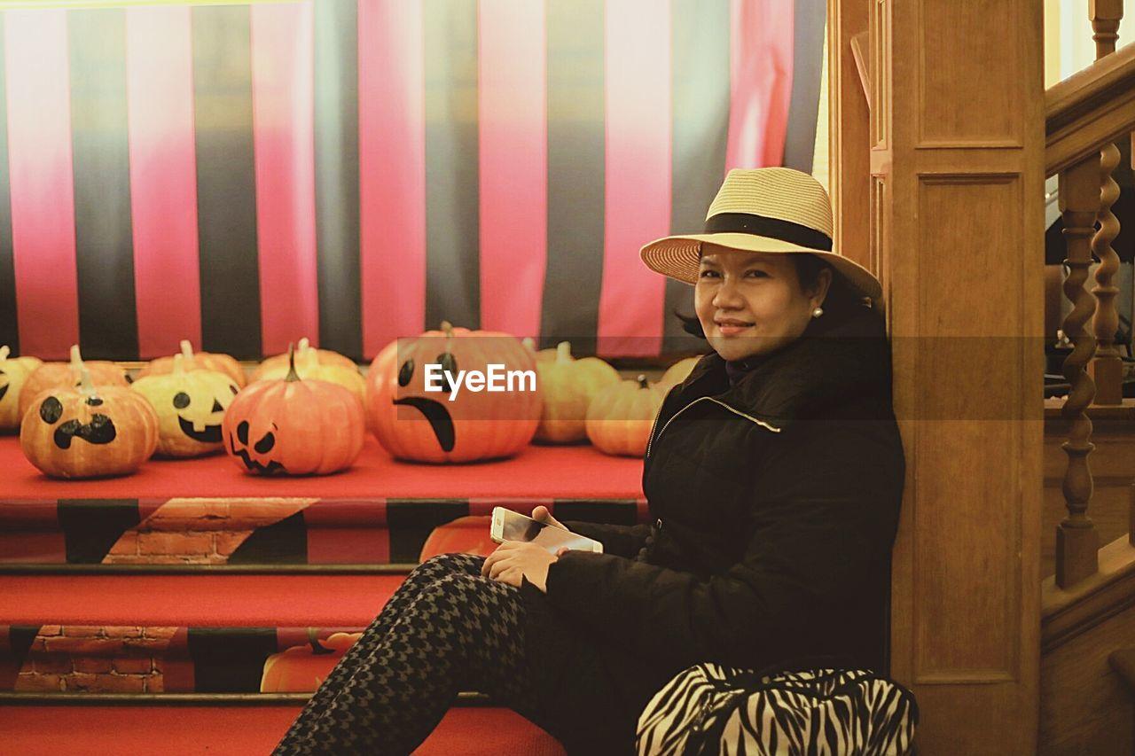 Side view portrait of woman sitting by jack o lanterns