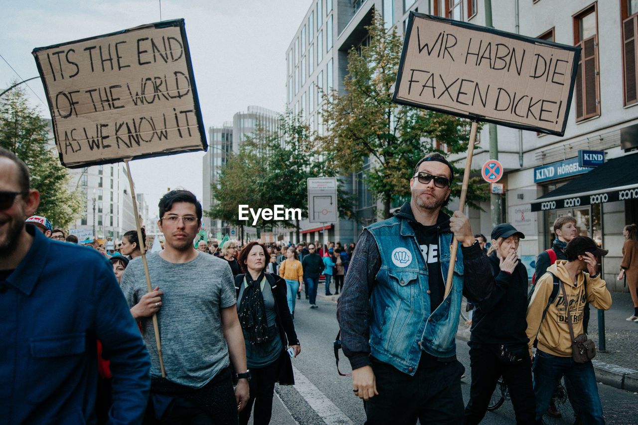 text, communication, group of people, men, protest, architecture, standing, city, adult, day, street, sign, people, real people, western script, casual clothing, building exterior, women, protestor, looking at camera, message