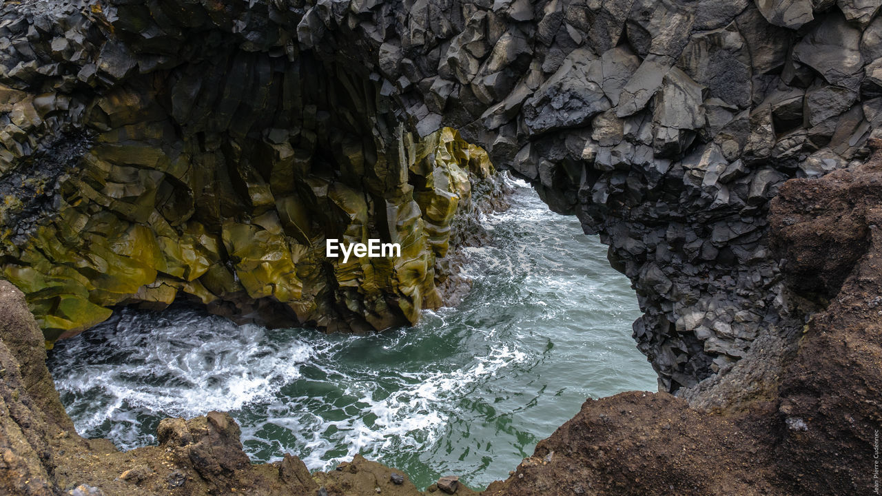 High angle view of sea under cliff
