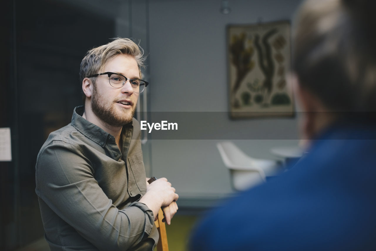 Confident male computer programmer talking to female colleague in office