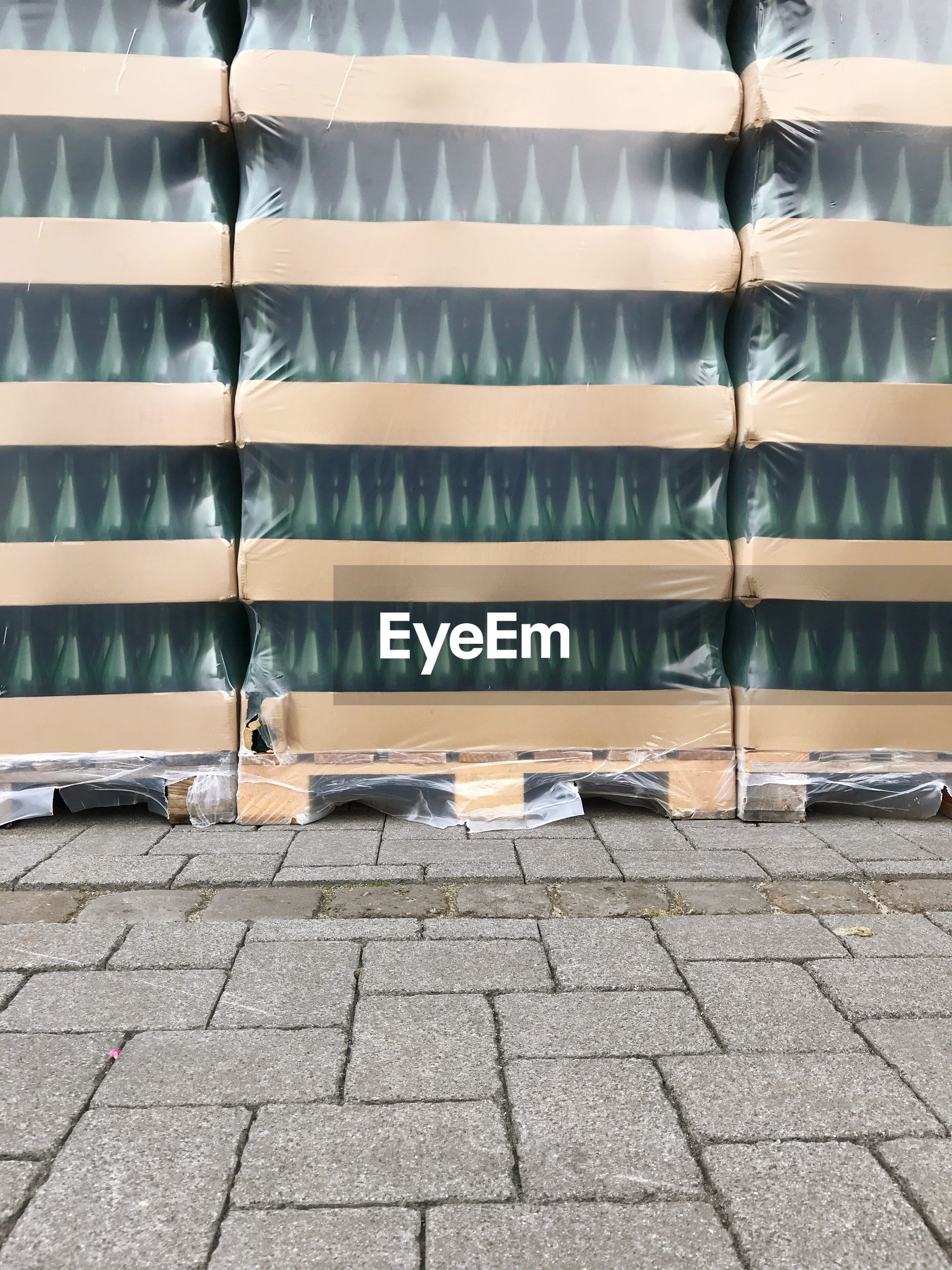Stack of packed bottles in crate on cobbled street