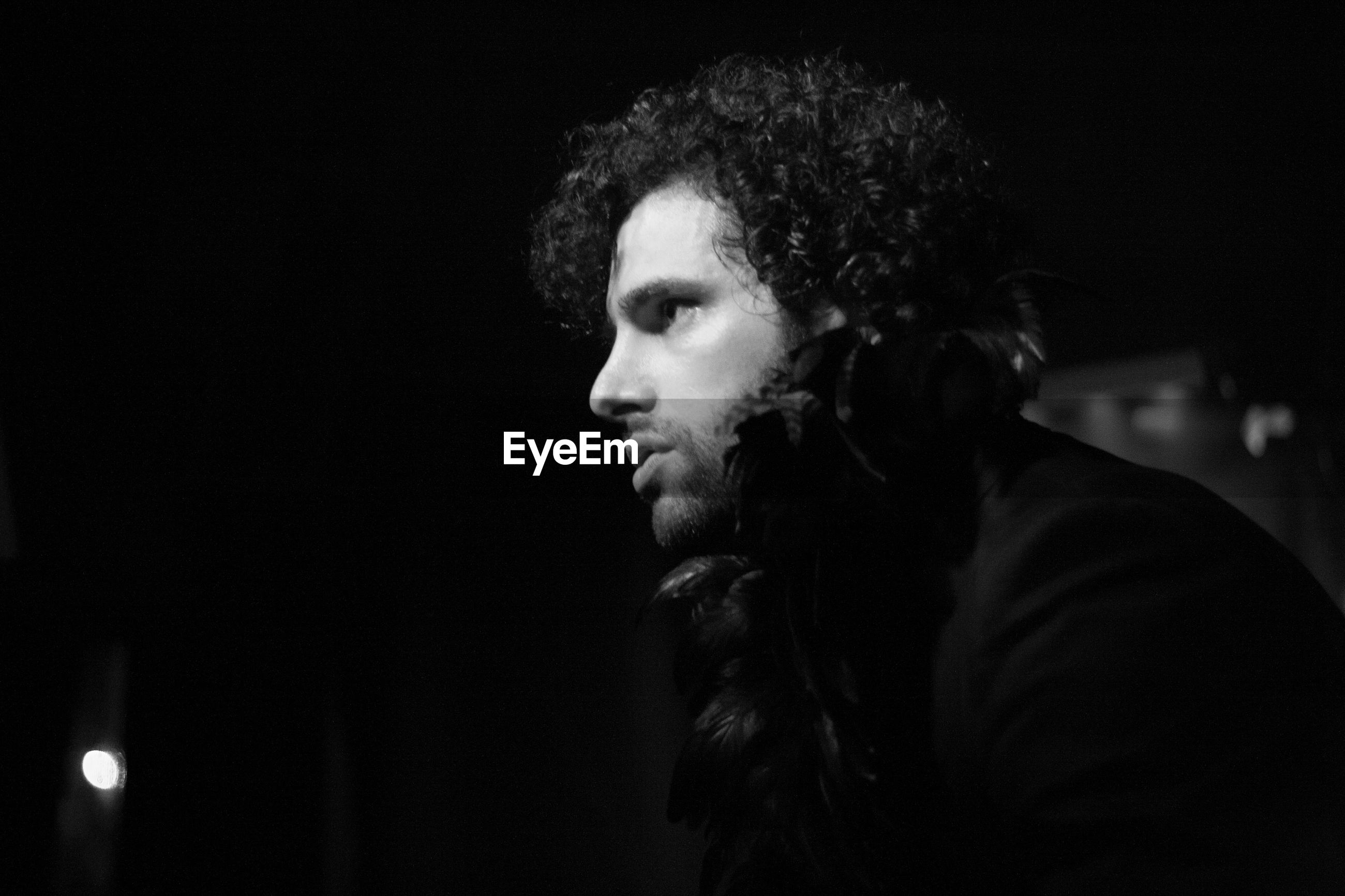 Man looking away in darkroom