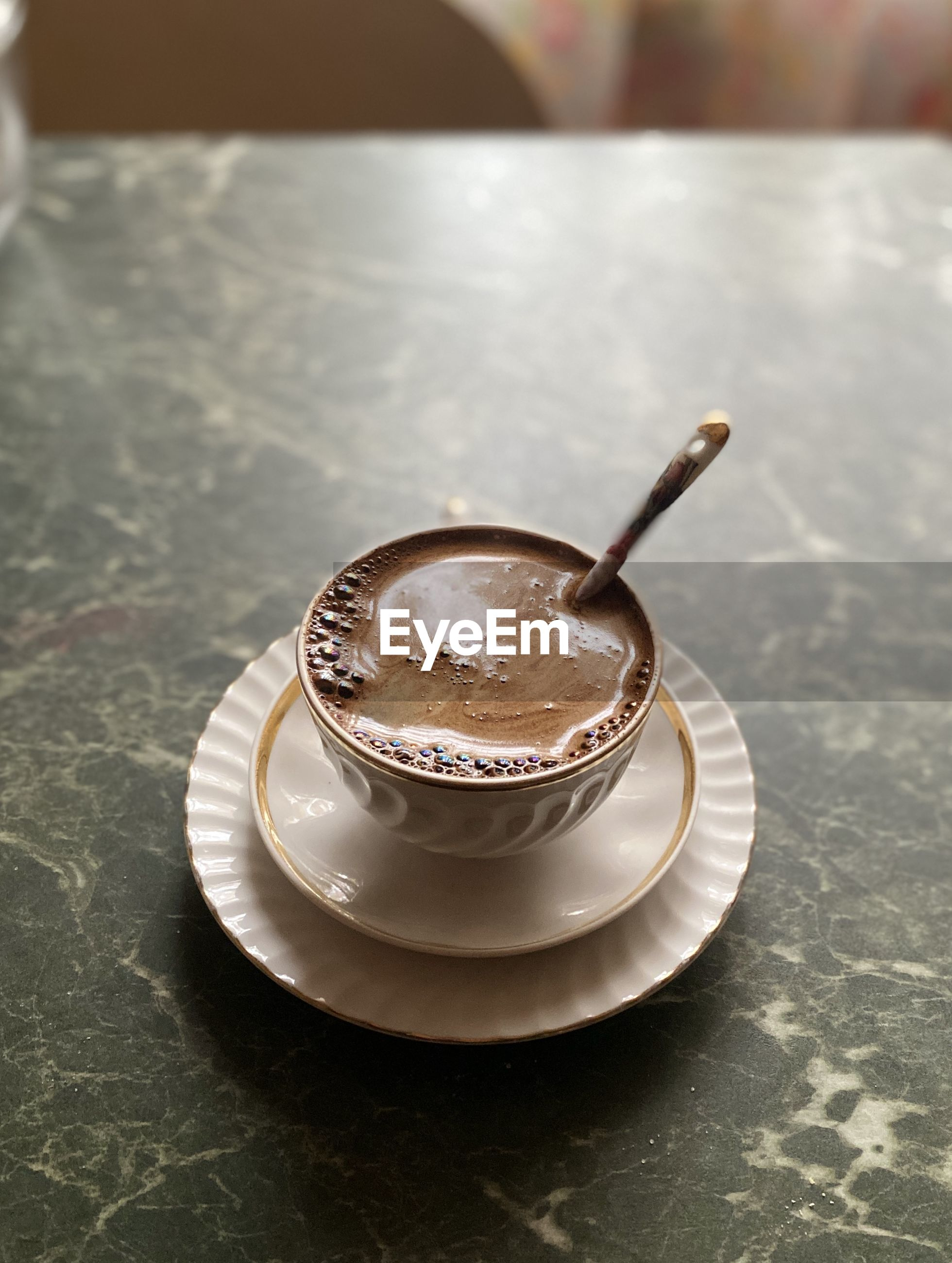 COFFEE CUP ON TABLE WITH SPOON