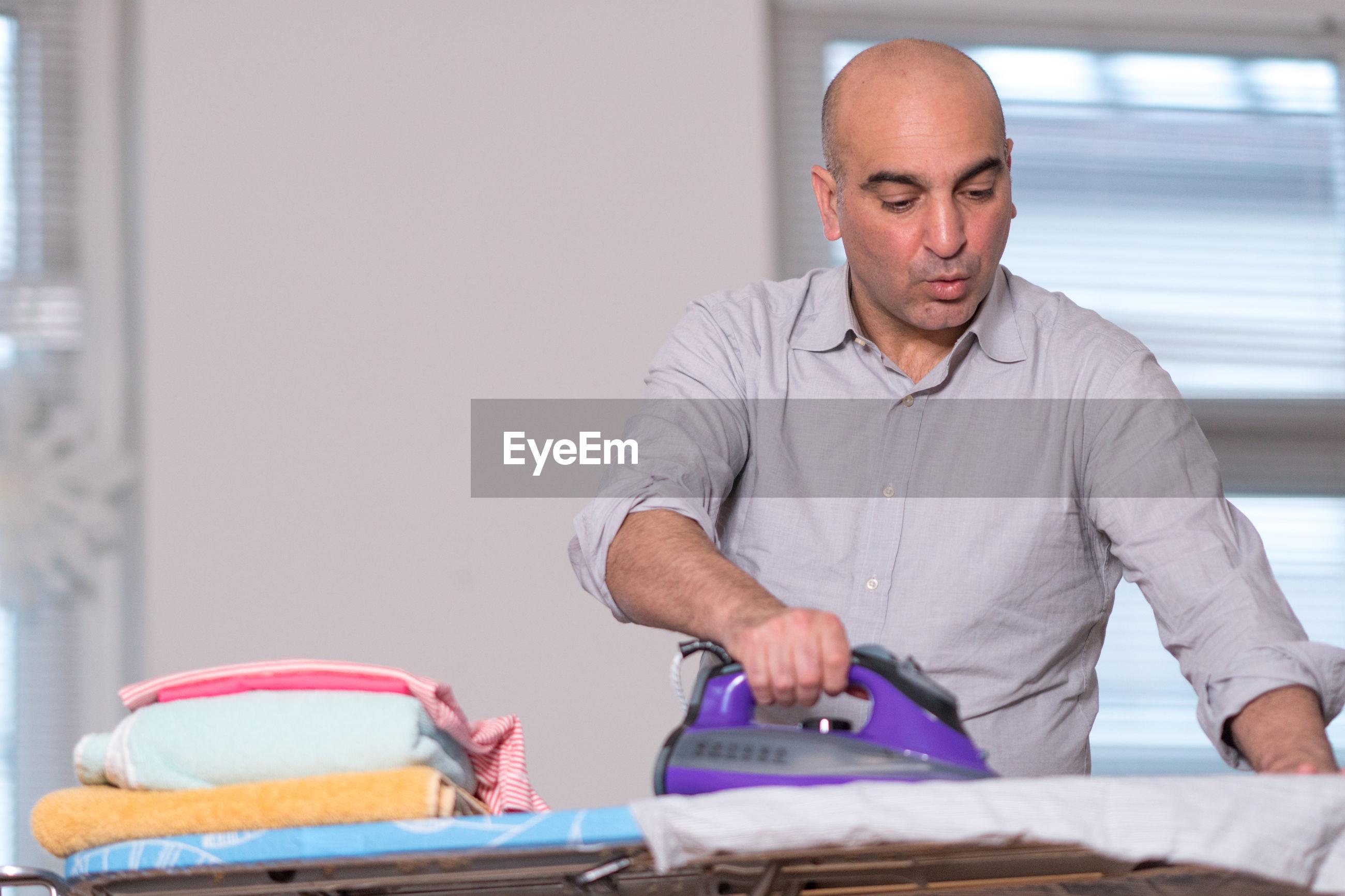 Man ironing clothes at home