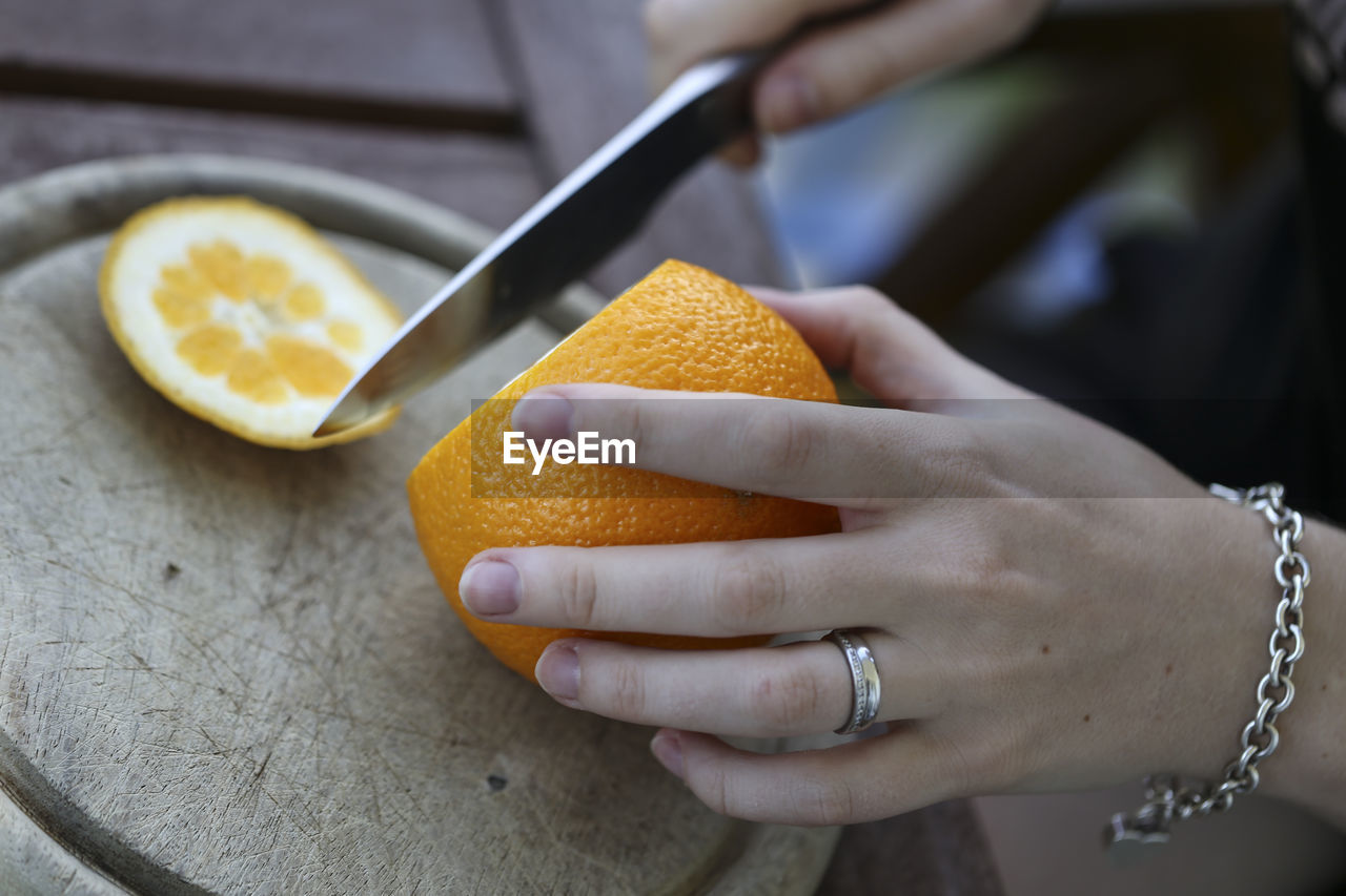 Cropped Hand Of Woman Cutting Orange In Plate At Home