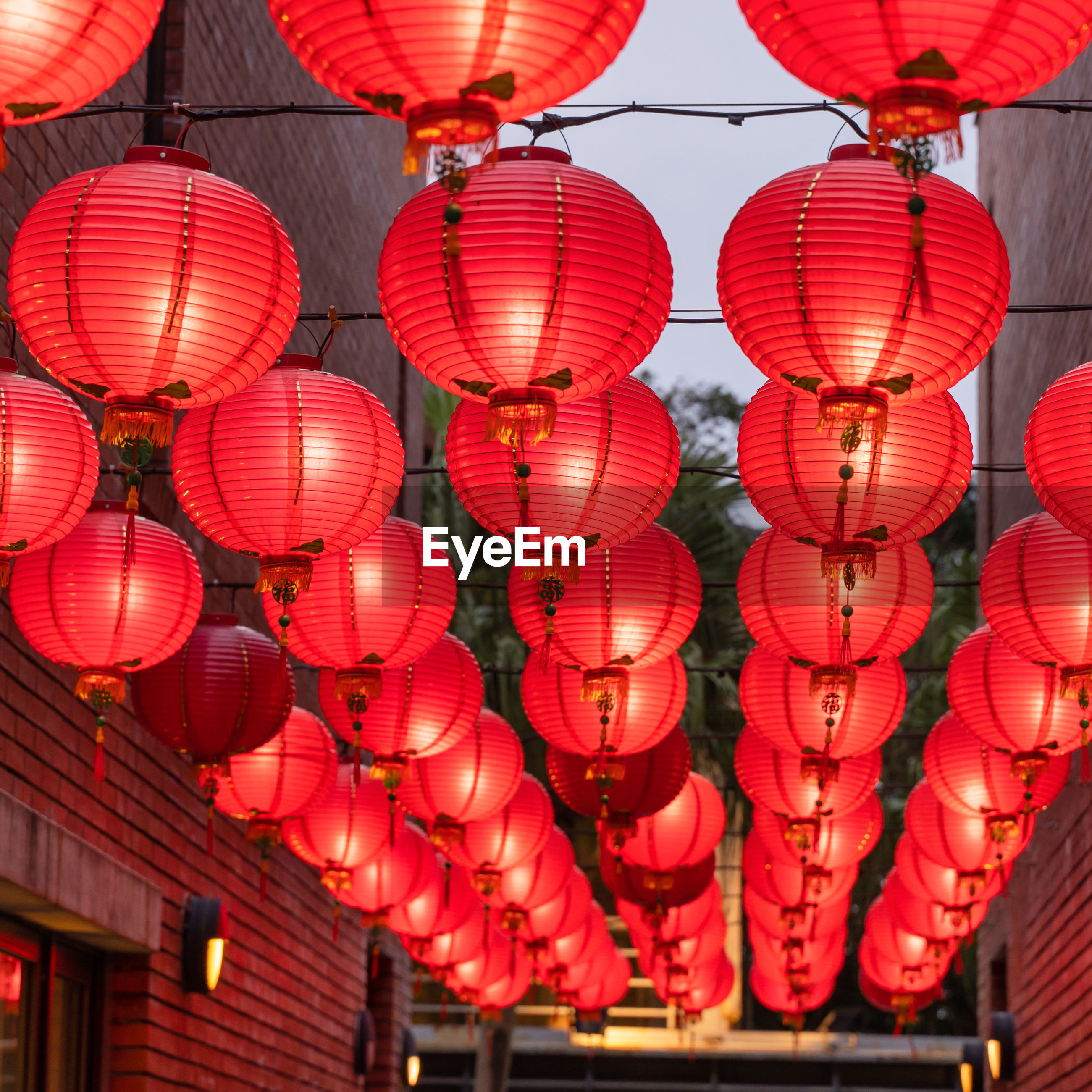 LOW ANGLE VIEW OF LANTERNS HANGING AT CEILING