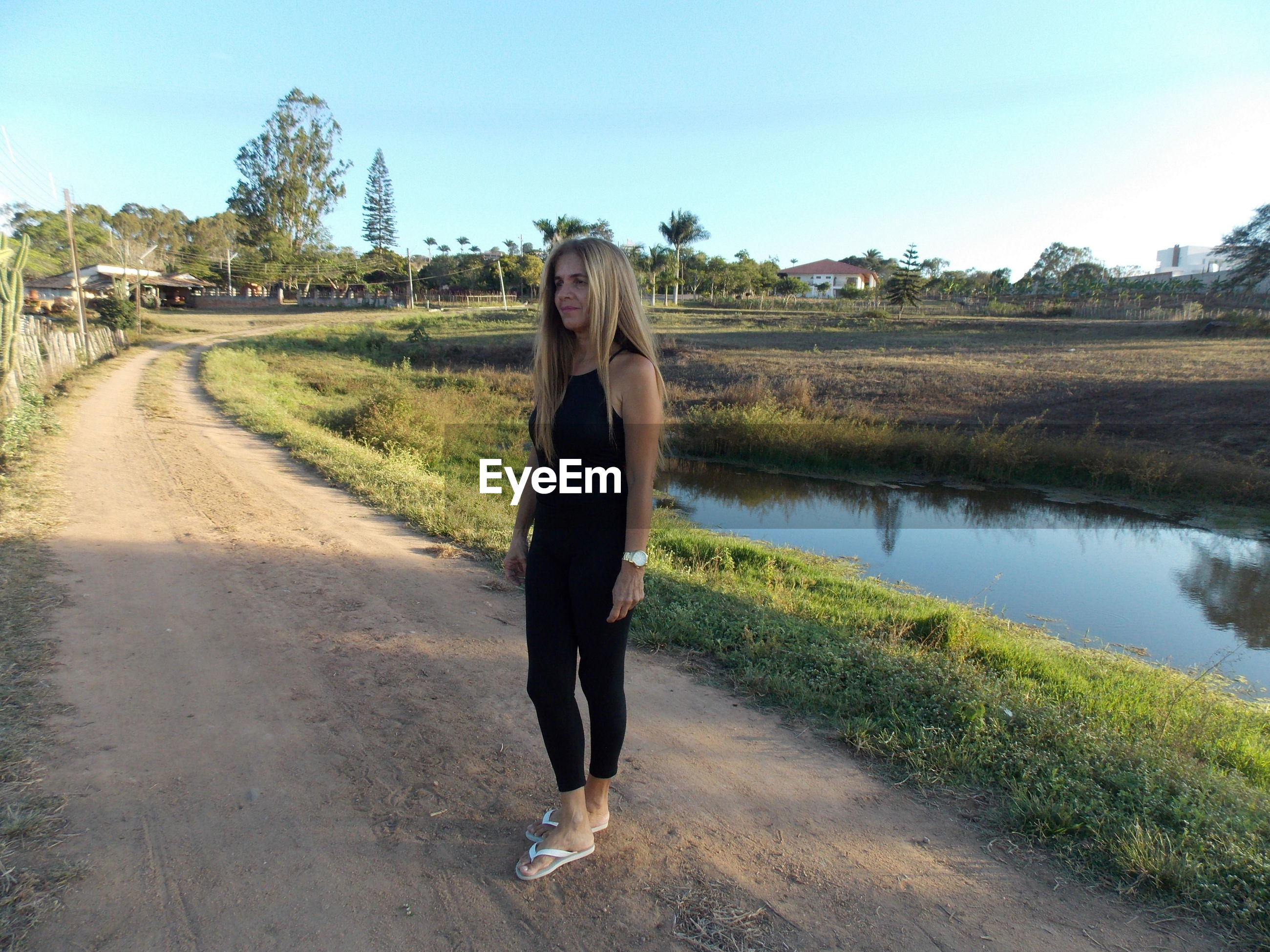 Full length of mature woman with long hair standing on dirt road against clear sky