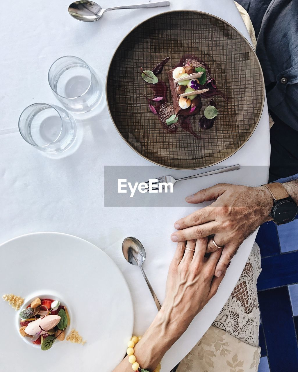 High Angle View Of Senior Couple Holding Hands At Table While Having Food