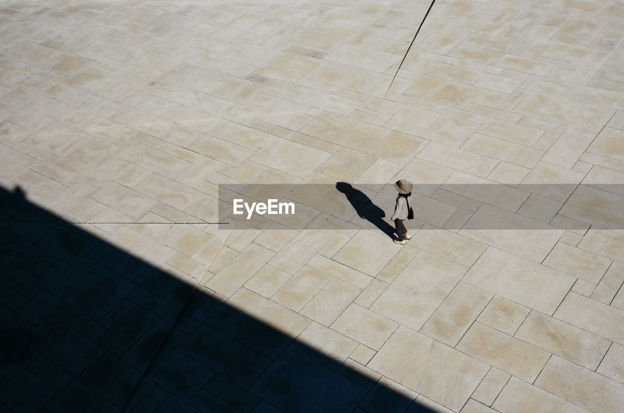 High Angle View Of Girl Walking On Pedestrian Zone During Sunny Day